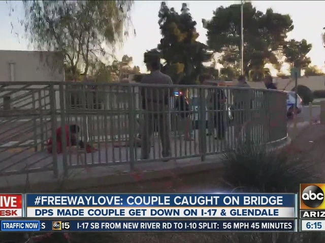 Couple talking with troopers after cuddling atop bridge