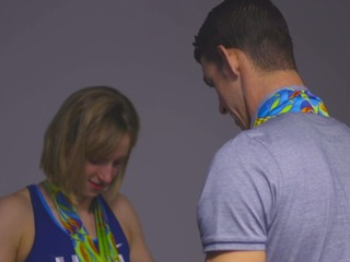 'Coach' Phelps helps Ledecky with medals for pic