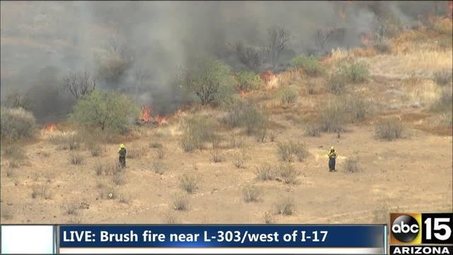 Crews battling brush fire along a freeway in north Phoenix